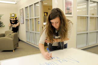 Philip Vukelich | Argonaut Campus Visit Office student worker Rylee Beasley changes the welcome whiteboard located in the University of Idaho Student Union Building Monday. The office helps recruit students to UI with campus tours and informational meetings for prospective students.