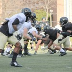 Yishan Chen | Argonaut  The offensive and defensive lines square off in a heated practice Wednesday on the SprinTurf.