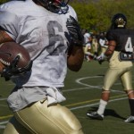 Senior running back Elijhaa Penny runs down the sideline during Friday's practice on the SprinTurf. Penny is expected to be Idaho's feature running back for the 2015 football season.