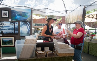 David Betts | Argonaut Allison Meyer goes over some of her photography with customers in her booth at the Farmers Market on Saturday July 4. The Farmers Market runs through October.