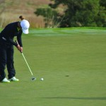 Michelle Kim freshman on the Womans Golf team at University of Idaho putting her ball into hole four.